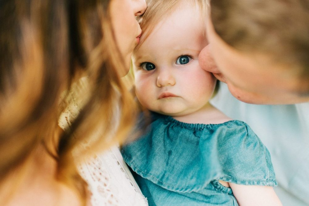 mom and dad kissing toddler girl with blue eyes