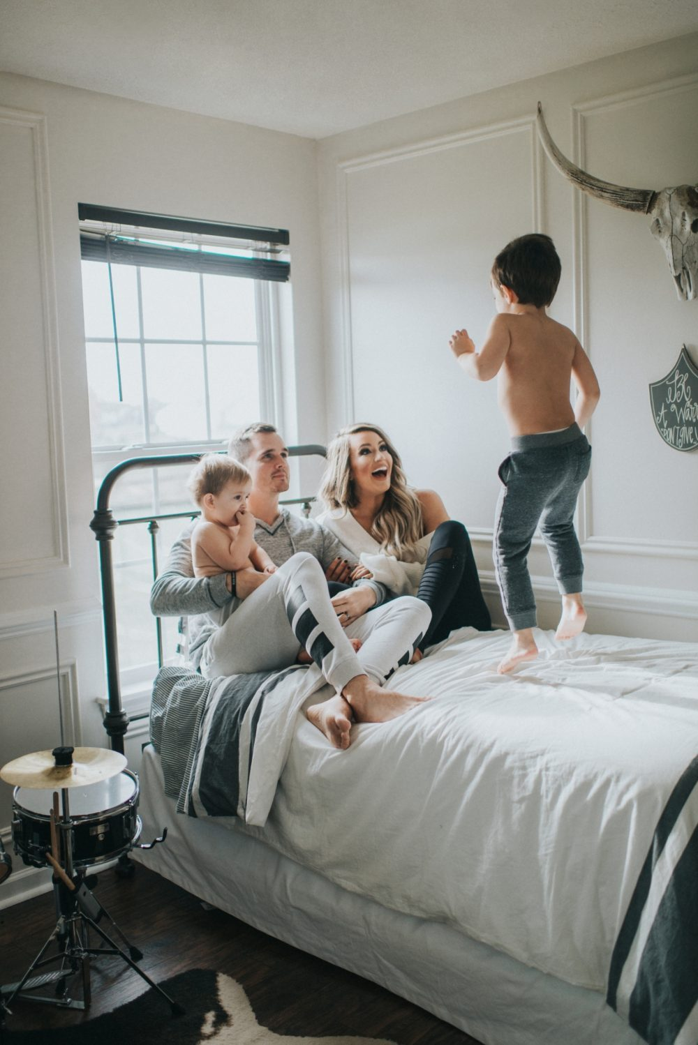 toddler boy jumping on bed with family