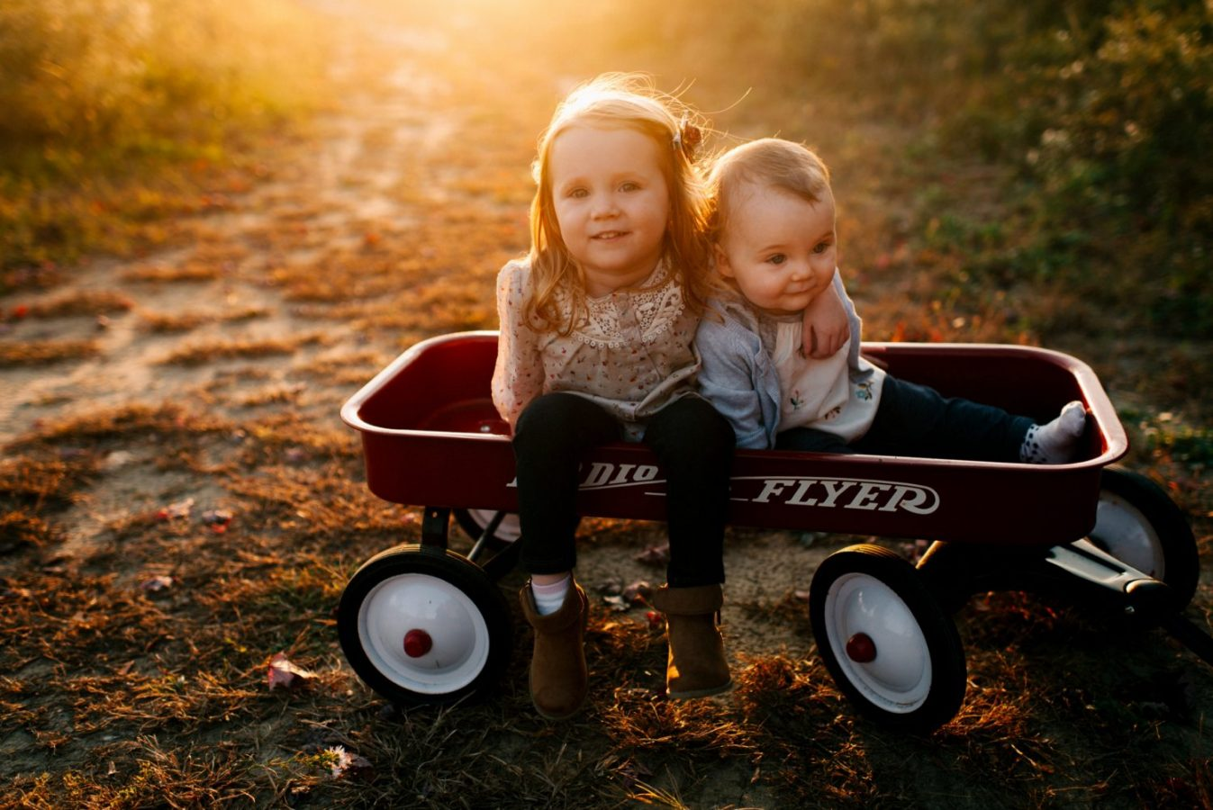 Sisters sitting in a wagon together at sunset