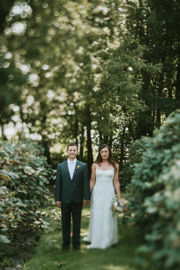 bride and groom holding hands in a vineyard