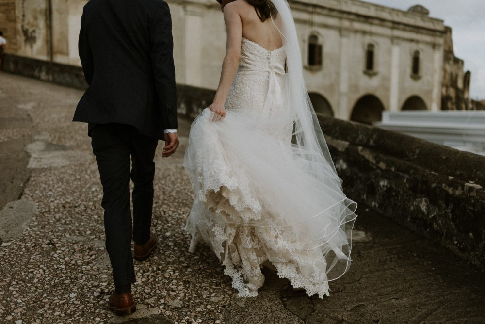 bride and groom walking up cobblestone street