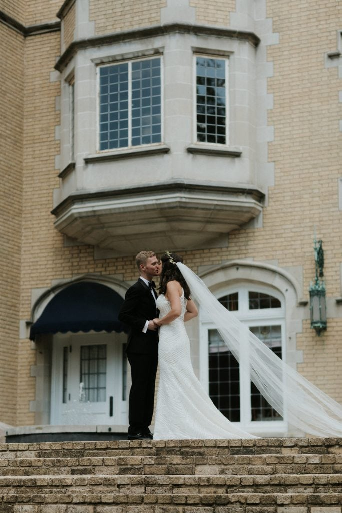 bride and groom standing in front of a mansion