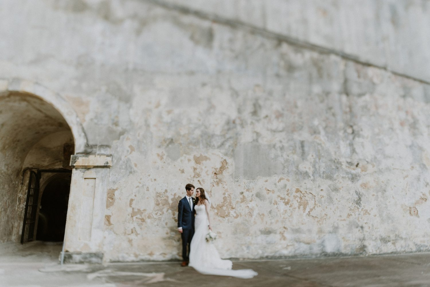 bride and groom standing against a castle wall