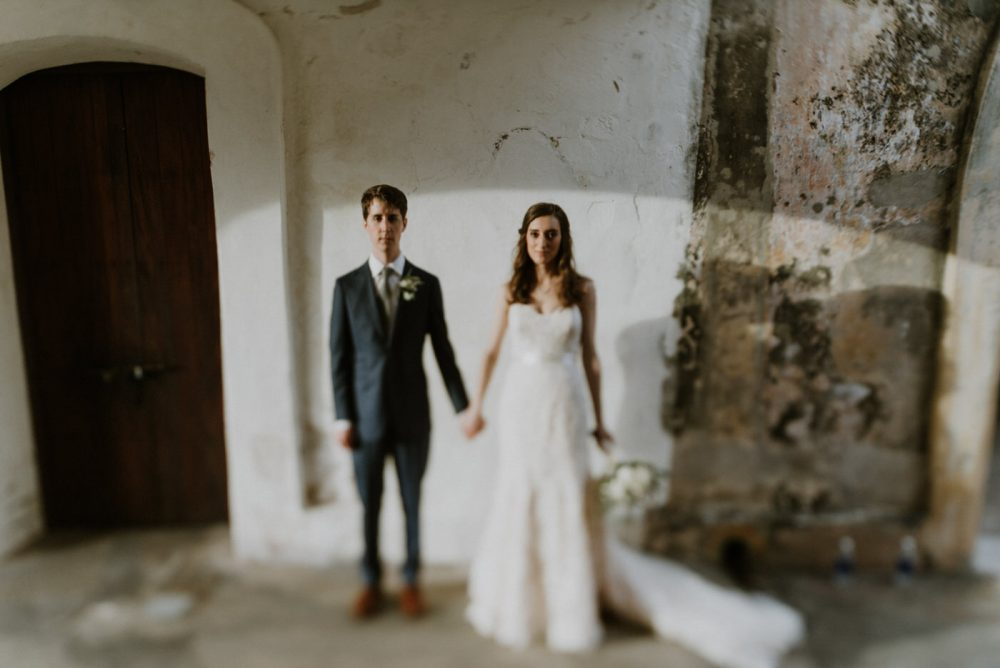 bride and groom holding hands in a castle