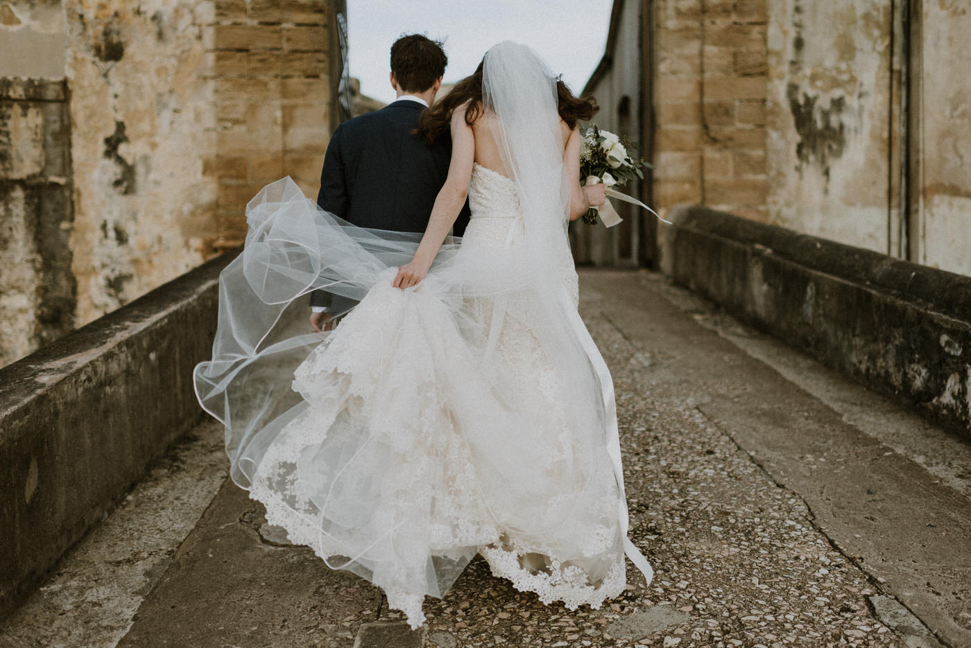 bride and groom walking along cobblestone path towards a castle