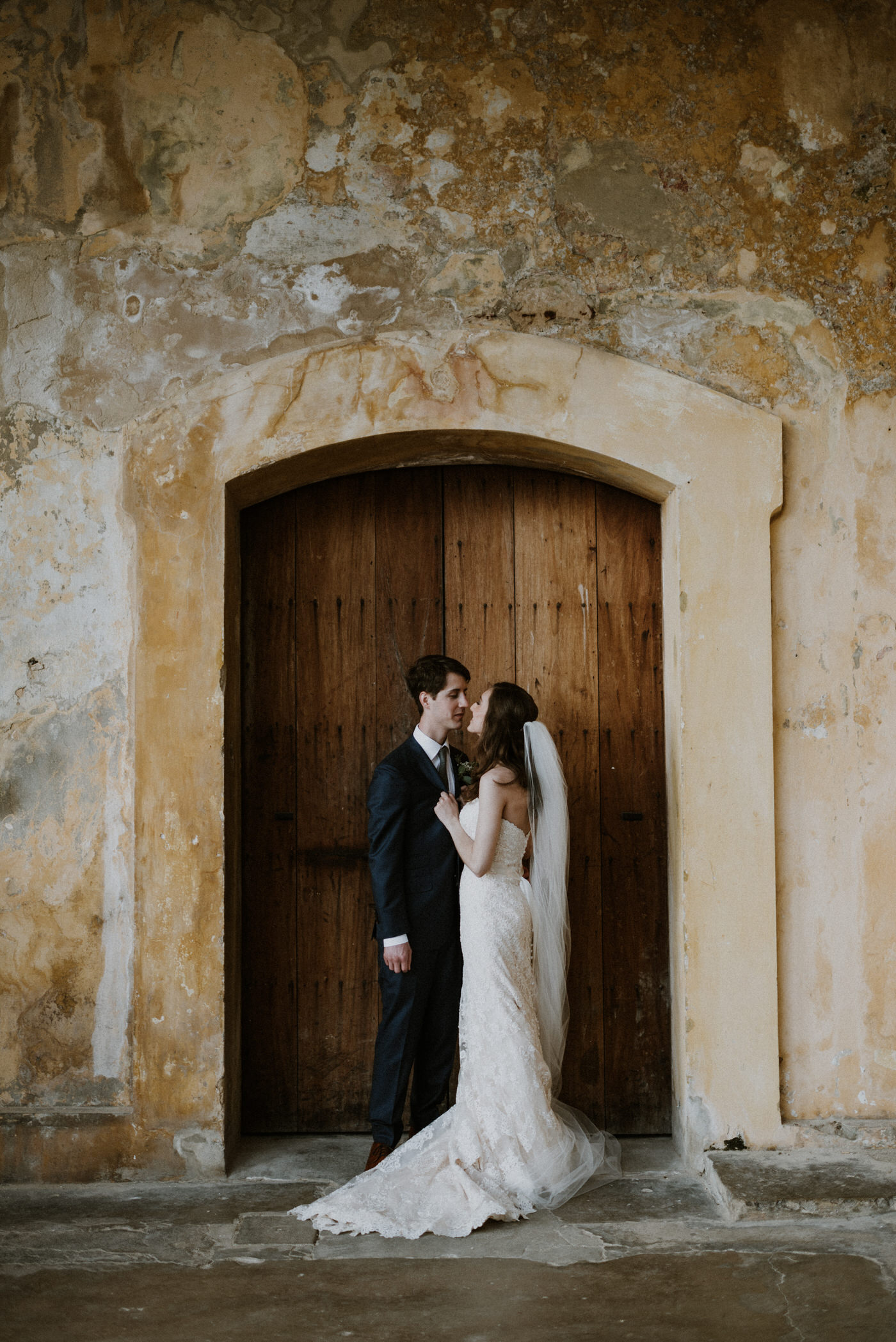 Beautiful bride and groom standing at a castle door