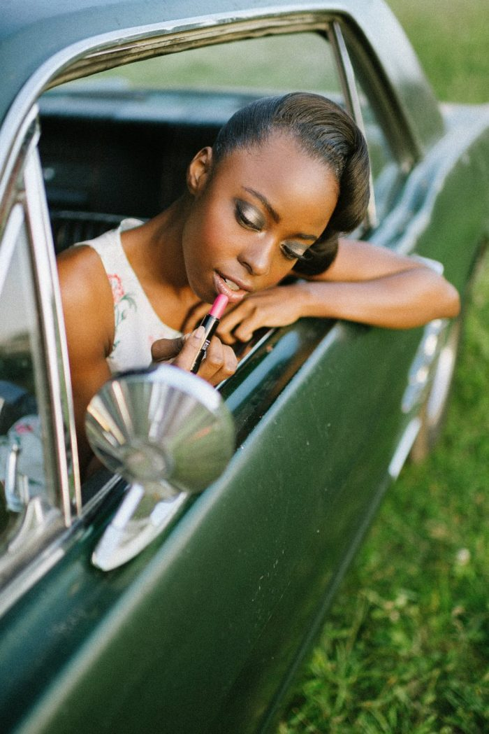 retro fashion model in antique muscle car
