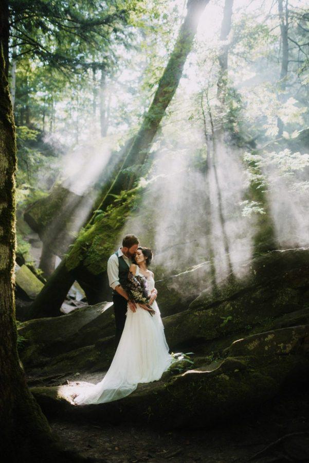 Beautiful bride and groom standing on rocks with sun shining