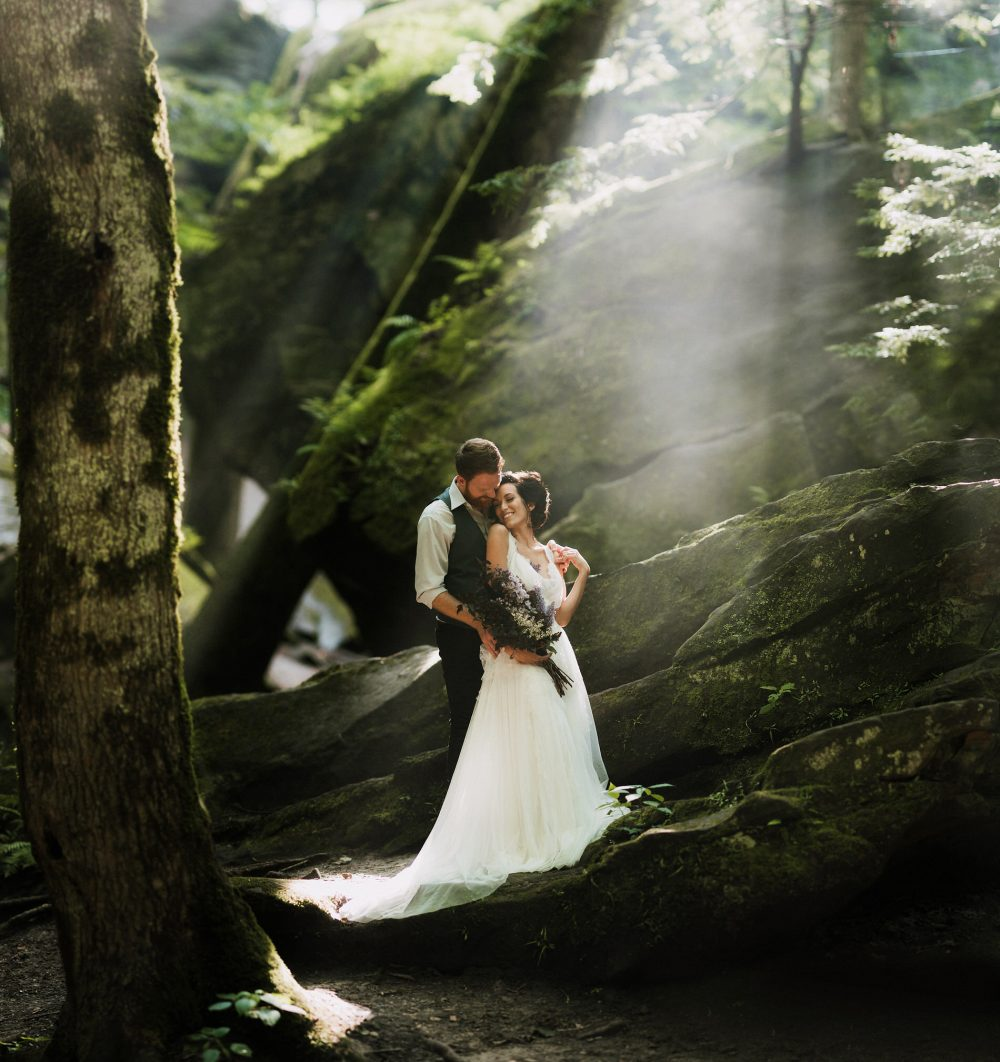 beautiful bride and groom standing amongst rocks