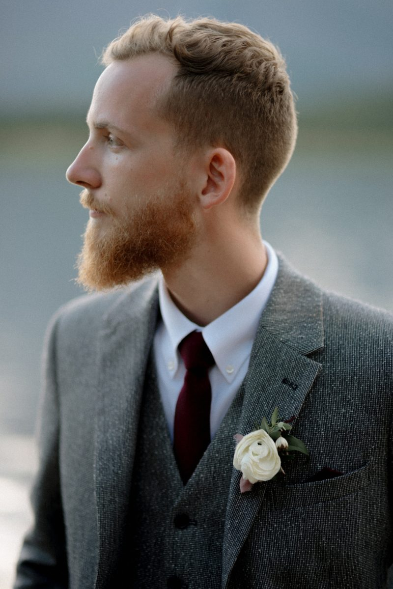 groom in gray suit and red tie