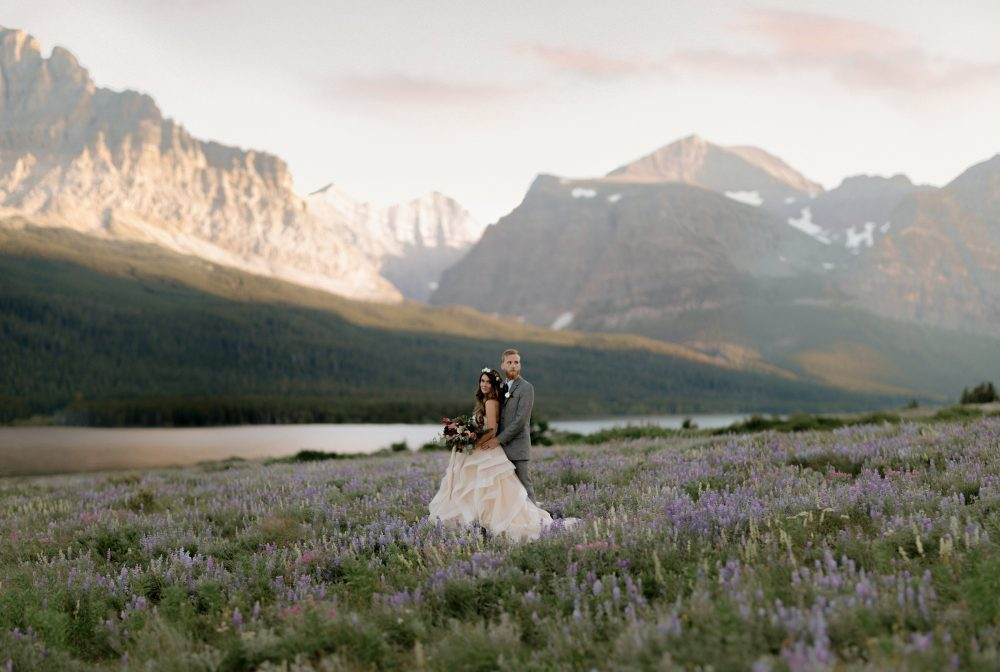 bride and groom standing in a flower field