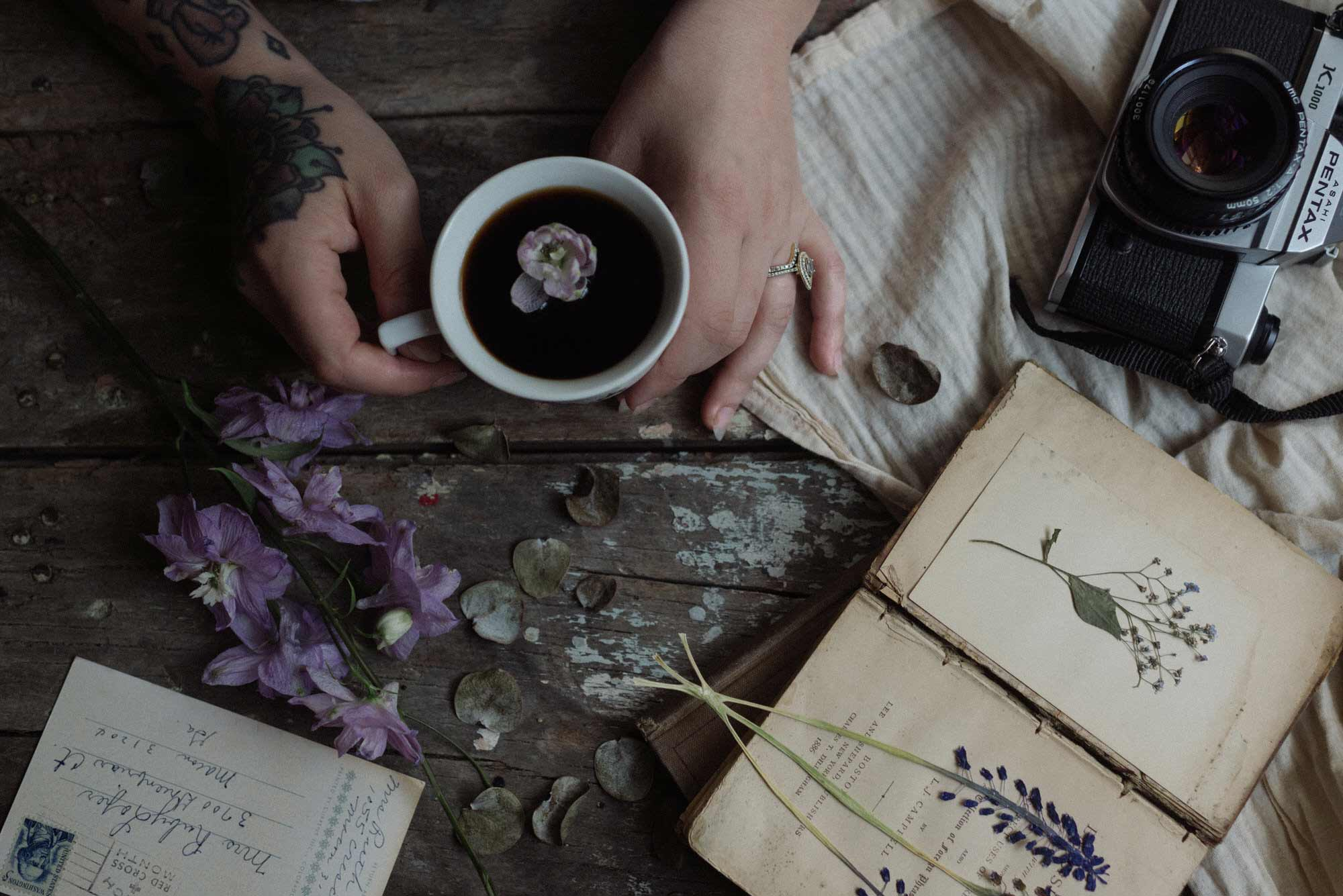 tattooed hand holding a cup of coffee with a flower in it