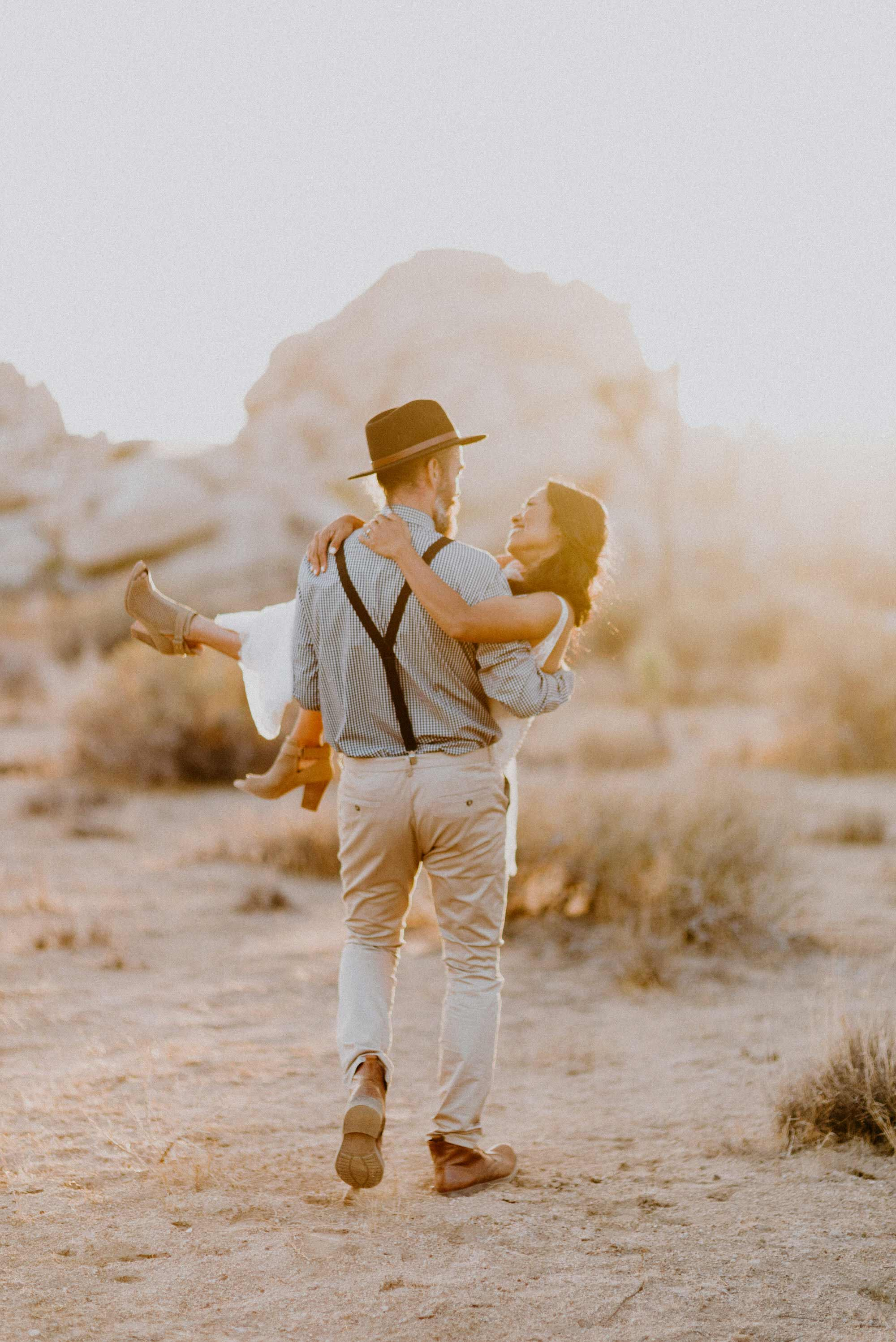 groom carrying bride in joshua tree national park